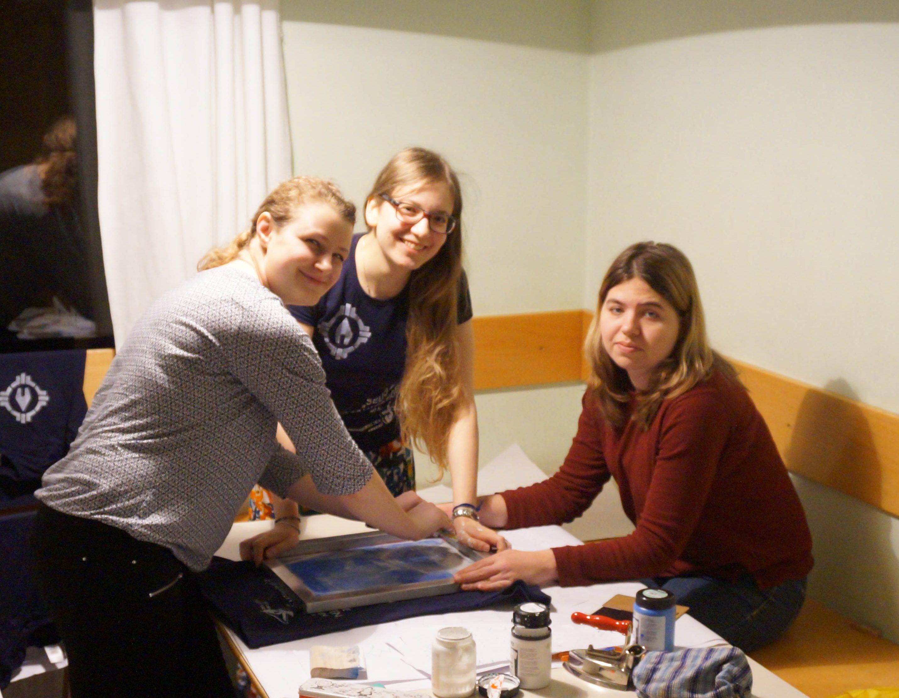 drei junge Frauen, die durch Siebdruck ein Shirt gestalten
