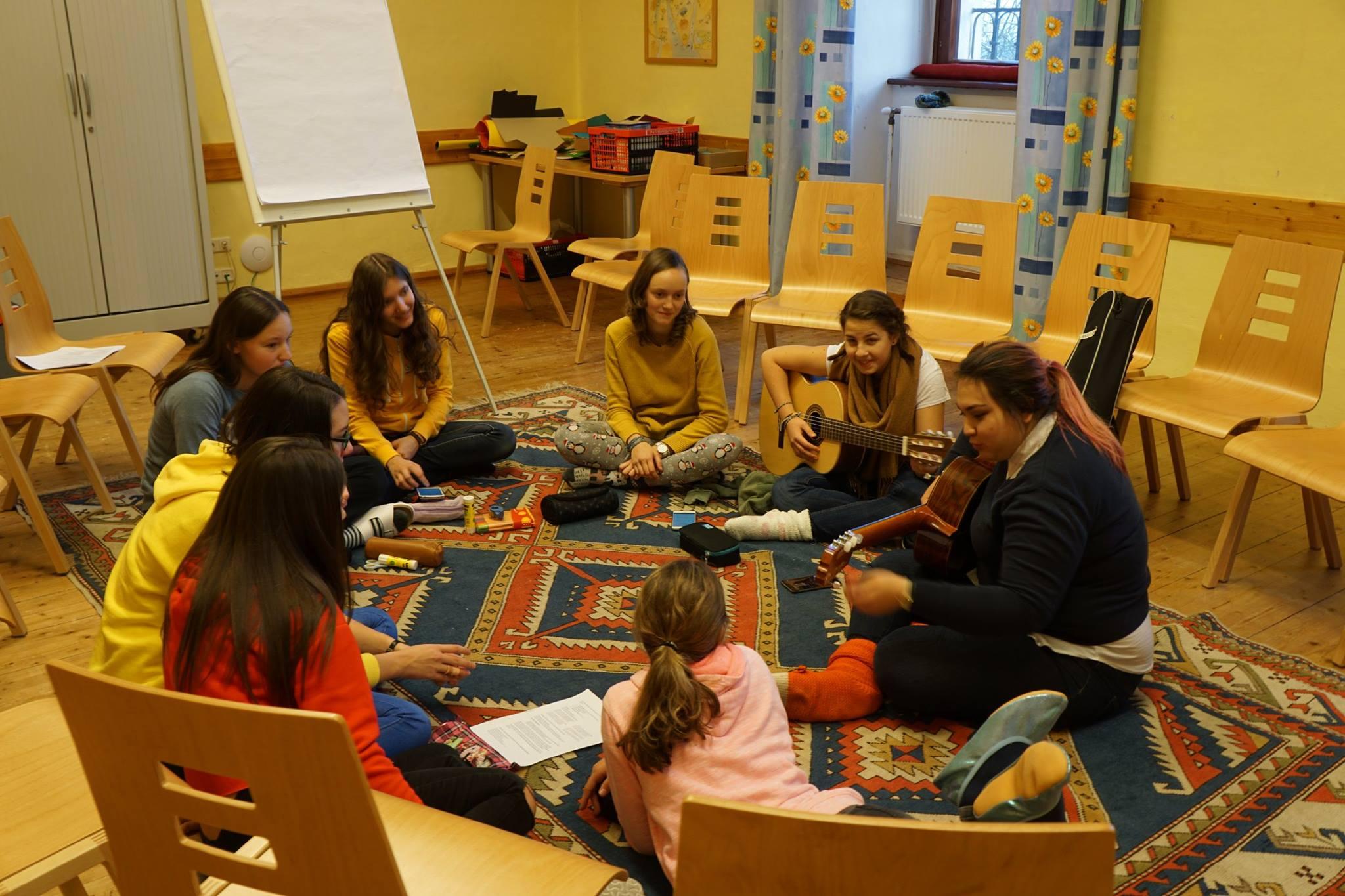 Einige, junge Mädchen sitzen im Kreis und singen zusammen!