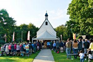 viele Menschen feiern gemeinsam vor dem Heiligtum die Hl. Messe