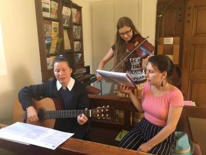 Marienschwester und junge Frauen singen und spielen Instrumente im Heiligtum